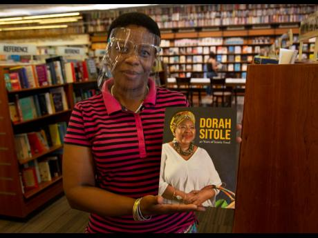 Bookshop  worker Dikeledi Nhlapo holds a copy of Dorah Sitole's '40 Years of Iconic Food' cookbook in  an Exclusive Books  store at Hyde Park Corner, Johannesburg. Sitole, South Africa's pioneer black food writer,  died this month of COVID-19.
