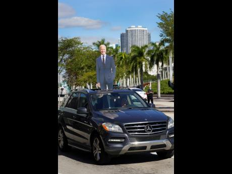 A motorist drives by with a cut-out of President Joe Biden near a site where others were watching the inauguration of President Joe Biden on a mobile screen on Wednesday, January 20, outside the famed Freedom Tower in downtown Miami.