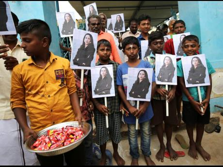 A child holds a tray of chocolates as others hold portraits of US Vice-President-elect Kamala Harris, after participating in special prayers ahead of her inauguration at a Hindu temple in Thulasendrapuram, the hometown of Harris' maternal grandfather, ye