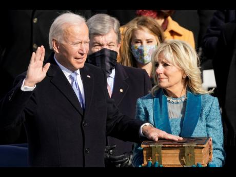 Joe Biden is sworn in as the 46th president of the United States by Chief Justice John Roberts as Jill Biden holds the Bible during the 59th Presidential Inauguration at the US Capitol in Washington yesterday.