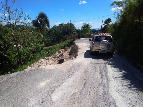 A motorist navigates one of three breakaways along the Jointwood main road in St Elizabeth, which residents want repaired urgently.