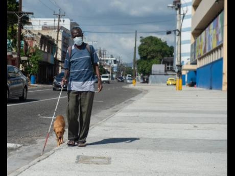 Herman McGregor, who is visually impaired, walks down East Street on Wednesday with man's best friend in tow. McGregor said the dog, which is not his, has taken a liking to his company after receiving helpings of food.