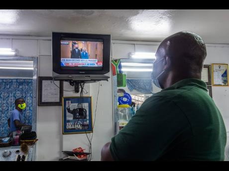 Christopher Reid, who works at A Class Barbers in Mona, St Andrew, watches the inauguration ceremony for Joseph Biden as the 46th president of the United States of America on Wednesday. Jamaicans' interest in the new administration has been piqued by Vic