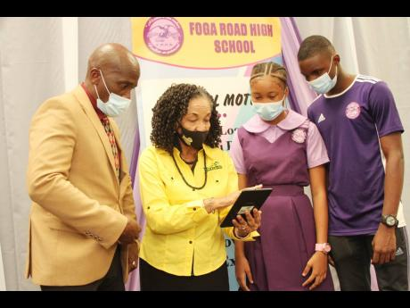 Jamaica Anti-Doping Commission Executive Director June Spence Jarrett (second left) goes through the features of a tablet with (from left) Foga Road High Principal Orett Wallace, netballer Kevaunna Tulloch and athlete Franklyn Tayloe as she handed over 25