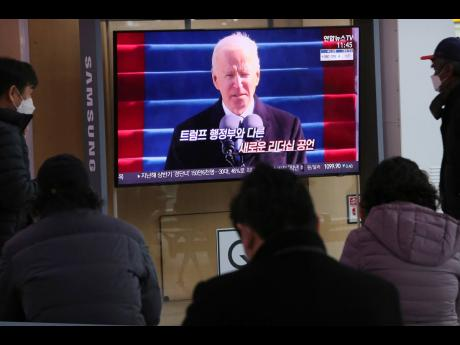 People watch a TV screen showing a news report about United States President Joe Biden's inauguration at the Seoul Railway Station in South Korea. The screen reads 'New leadership'.