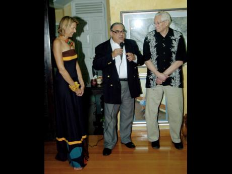 Robert MacMillan (centre) turned emcee for the launch of good friend Ronnie Nasralla's book. The launch was held at the home of Susan Dougall (left).