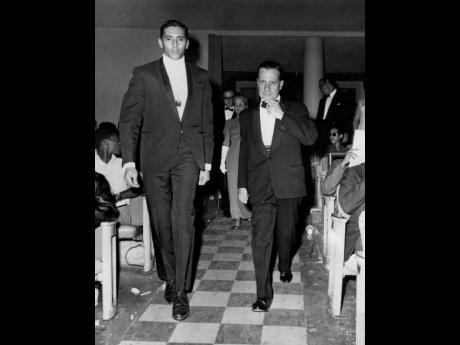 Acting Governor General, Sir Herbert Duffus (right), followed by Lady Duffus (in background) is escorted by Ronnie Nasralla, chairman of the Nuggets for the Needy Drive, into the Regal Theatre ahead of the show. Nasralla died on Wednesday at his Atlanta, G