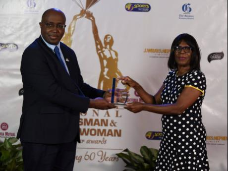 RJRGLEANER Sports Foundation Chairman Gary Allen (left) presents the Chairman's Award to Vilma Charlton during the hour-long broadcast of the RJRGLEANER Sports Foundation National Awards ceremony last night.