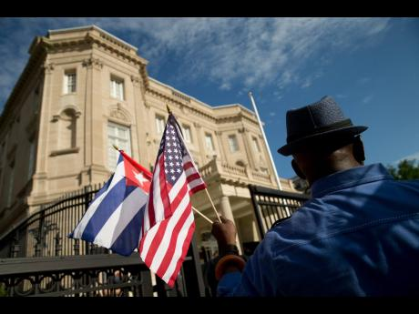 Edwardo Clark, a Cuban-American, holds an American flag and a Cuban flag as he celebrates outside the new Cuban Embassy in Washington, Monday, July 20, 2015.