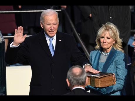 Joe Biden is sworn in as the 46th president of the United States by Chief Justice John Roberts as Jill Biden holds the Bible during the 59th Presidential Inauguration at the US Capitol in Washington on Wednesday.