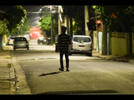 A lone figure walks along Alexander Road in Whitfield Town, Kingston, more than an hour after a 6 p.m. curfew was imposed in the community last October because of a rise in coronavirus cases and deaths.