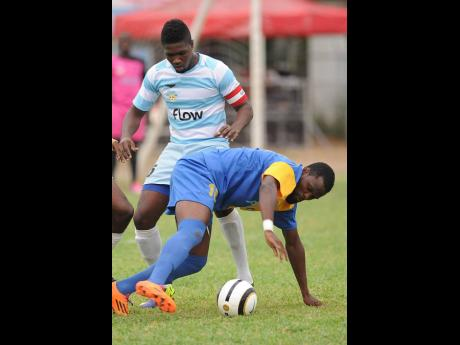 Alburn Facey (background) makes a tackle on Harbour View's McKaully Tulloch, while representing Reno in the Premier League in November 2014.