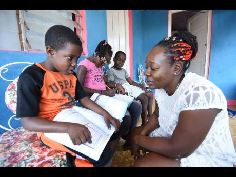 Nine-year-old Ricardo Grant (left) is assisted by his mother, Lashanna Junior, with schoolwork in Epsom, St Mary. In the background are Ricardo's siblings, Malaika and Orville, who also attend the Epsom Primary School. Residents of the area complain abou