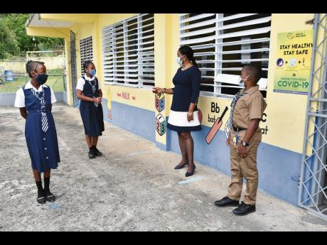 Guidance counsellor at the Salem Primary and Junior High School in Westmoreland, Sophia Mullings (second right), engages with grade six students (from left) Roshae Smith, Shevonise Tomlinson and Nickoli Lowers, while observing the social distancing protoco