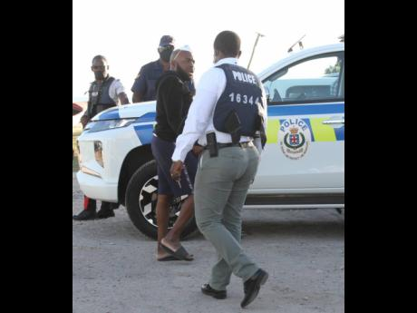 Businessman Nicholas Graham, who had been detained by the police on Sunday, is ushered to a police service vehicle after another search was conducted on his home in Rocky Point, Clarendon, on Tuesday, days after a mystery plane crash-landed in the seaside