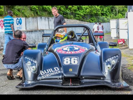 Veteran racer David Summerbell looks on as Bajan racer Mark Maloney gets last-minute instructions from his crew.