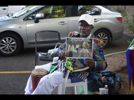 Seated on the grounds of the Bob Marley Museum, Bongo Herman pulled out a laminated image of himself playing football with Bob Marley.