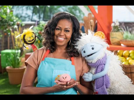 Former First Lady Michelle Obama with Busy, a bee puppet, Mochi, a pink round puppet, and Waffles, a furry puppet with waffle ears, on the set of the children's series 'Waffles + Mochi'.  Obama is launching the new Netflix children's food show on March 1