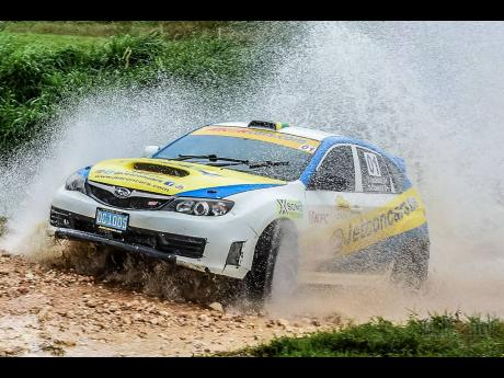 Joel Jackson and his Subaru WRX rallycar exits the watersplash  rally stage in the Tru Juice orchards.