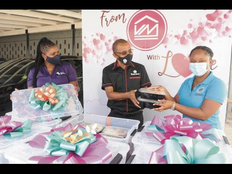 Hotiyana Brown (right) is all smiles as she is presented with meals for residents of the Marie Atkins Night Shelter by Courtney Campbell, group president and CEO, Victoria Mutual Group. At left is Clover Moore, assistant vice-president, group corporate aff