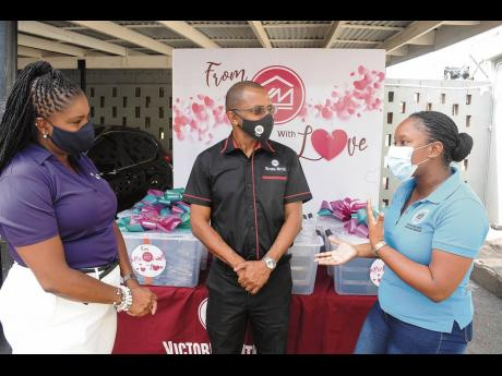 Hotiyana Brown (right), expresses gratitude to Clover Moore (left), assistant vice-president, group corporate affairs and communications, Victoria Mutual Group; and Courtney Campbell, group president and CEO, following the presentation of the items.