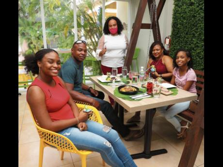 Nicola Speid (centre), SME business banker, Sagicor Bank, is pictured with (from left) Ashleigh Stampp, Jerome Stampp, Dawn Ruddock and Alexia Stampp, at the Julie Mango restaurant, after the family was informed that their meal would be covered by Sagicor