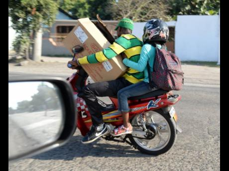 In this 2016 file photo, two men are seen riding a motorbike, trying to manoeuvre the traffic and balance the box on his lap at the same time.