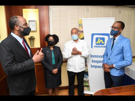 Earl Jarrett (left), deputy chair and chief executive officer of The Jamaica National Group, explains to Russell Barrett (right) the importance of the Oliver Clarke Graduate Scholarship. Meanwhile, Parris Lyew-Ayee (second right), chairman of the JN Founda