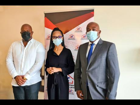 Acting General Manager of the Professional Football Jamaica Limited, Arlene Martin (centre), shares lens time with Kemtech Development and Construction executives Karl Tulloch (left) and Garwin Tulloch. Kemtek recently signed on as a club sponsor of the Ja