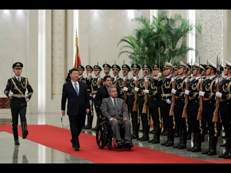 In this December 12, 2018 file photo, President of China Xi Jinping (second left) walks beside President of Ecuador Lenin Moreno as they review an honour guard during a welcome ceremony at the Great Hall of the People in Beijing, China.