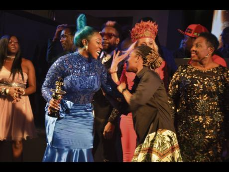 Entertainers Spice (left) and Koffee celebrate their wins, as Minister of Culture, Gender, Entertainment and Sport Olivia Grange looks on.