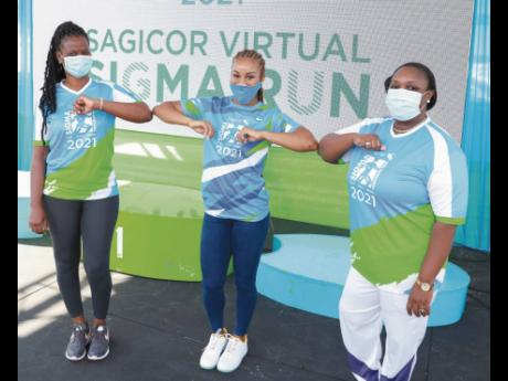 Briana Williams, 2021 Sagicor Sigma Run 2021 race patron and World Under-20 sprint double champion, bumps elbows with Annotto Bay Hospital CEO Marsha Lee (left) and Port Antonio Hospital CEO Althea Gardner.