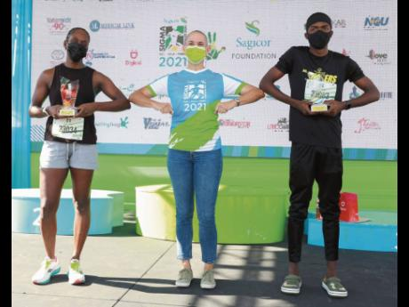 Cathy Allen (centre), Sagicor's chief actuary, congratulates the overall winners in the Sagicor Sigma Run Invitational event, Joanne Harris (left) and distance runner Kevroy Venson from Calabar High School.