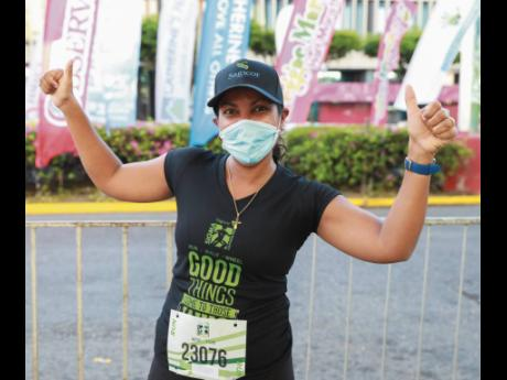 Corrinne Bellamy, assistant vice- president and employee benefits administrator, actuarial services, Sagicor, gives two thumbs up following her successful completion of the 5.5 km route.
