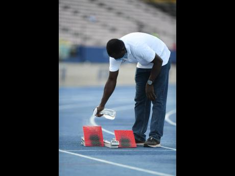 An official sprays a starting block with what appears to be sanitising liquid at the Velocity Fest track meet, held at the National Stadium on Saturday, August 8, 2020.