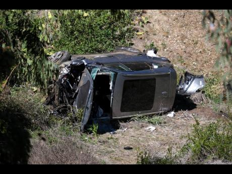 A vehicle rests on its side after a rollover accident involving golfer Tiger Woods along a road in the Rancho Palos Verdes section of Los Angeles yesterday. Woods suffered leg injuries in the one-car accident and was undergoing surgery, authorities and his