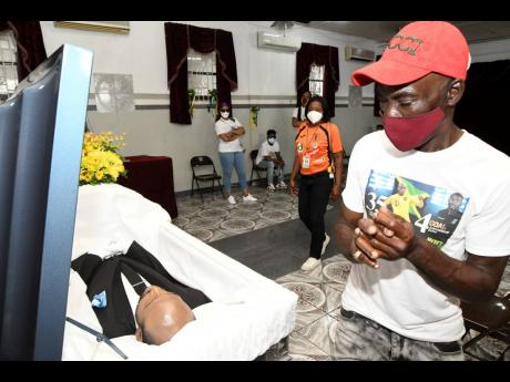 Rudolph Brown/Photographer A man views the boby of Luton Shelton at the House of Tranquility Funeral Home on Orange Street, in Kingston on Wednesday, February 24, 2021.