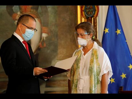 European Union Ambassador to Venezuela Isabel Brilhante Pedrosa is presented with a letter of 'persona non grata' from Venezuelan Foreign Minister Jorge Arreaza at his office in Caracas, Venezuela, yesterday. (AP)