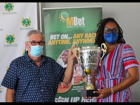 Five-time Triple Crown-winning trainer Phillip Feanny (left) poses with the inaugural Portmore Cup with Lorna Gooden, General Manager of Supreme Ventures Racing and Entertainment Limited, at the press launch of the Road to the Triple Crown and Triple Crown