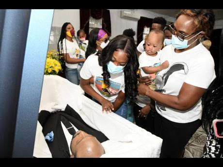 Bobbette Shelton (centre), wife of the late Jamaican footballer Luton Shelton, views the body of the former national striker along  with members of the family at the House of Tranquility Funeral Home on Orange Street in Kingston yesterday.