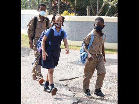 Three students from the Lititz Primary School in St Elizabeth walk along the main road on their way home from school yesterday. Education Minister Fayval Williams has announced that only students who are to sit major examinations should be allowed to parti