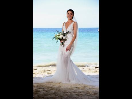 Her hair in a chignon, bride Leah Keiser wore a beautiful mermaid cut wedding dress with a plunge neckline.