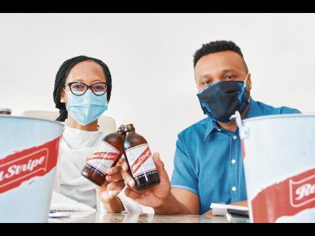 Arlene Martin (left), acting general manager of Professional Football Jamaica, signs with Nathan Nelms, Red Stripe brand manager, as the beer company confirmed its support for the Jamaica Premier League.