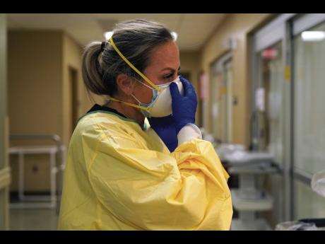 In this November 24, 2020, file photo, registered nurse Chrissie Burkhiser puts on personal protective equipment as she prepares to treat a COVID-19 patient in the in the emergency room at Scotland County Hospital in Memphis, Missouri.