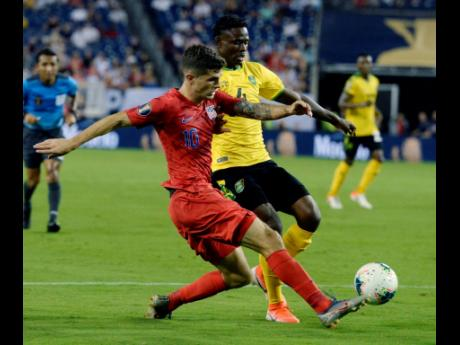 United States midfielder Christian Pulisic (left) kicks the ball past Jamaica midfielder Andre Lewis during the second half of a CONCACAF Gold Cup semi-final match on Wednesday, July 3, 2019, in Nashville, Tenn. The United States won 3-1. (AP Photo/Mark Za