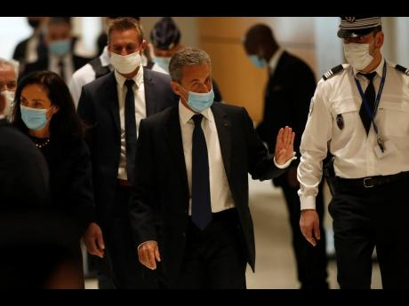 Former French President Nicolas Sarkozy (second right) arrives at the courtroom on March 1 in Paris.