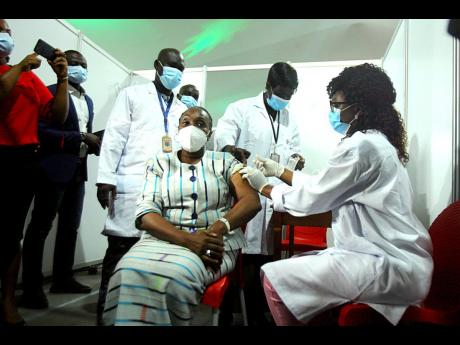 Raimonde Goudou Coffie, culture minister, receives a shot of the AstraZeneca vaccine in Abidjan, Ivory Coast, yesterday. Ivory Coast is the second country in the world after Ghana to receive vaccines acquired through the United Nations-backed COVAX initiat