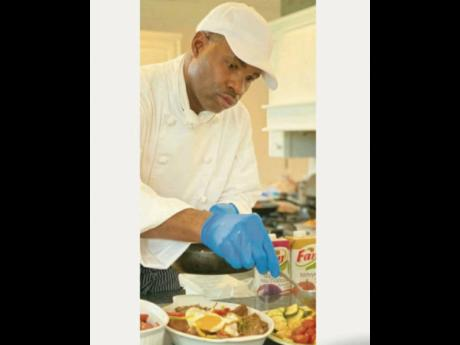 Chef Everton Smith puts the finishing touches to one of his delectable masterpieces.