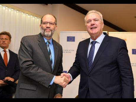 CARICOM Secretary General Irwin LaRocque (left), shakes hands with European Commissioner for International Cooperation and Development Neven Mimica after signing five agreements for multisectoral support for CARIFORUM in this April 2019 photograph.