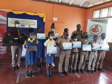 Rev Gary Harriott (left), chairman of the Robin's Hall Primary School board and students of the school pose with tablets and laptops donated by past students of the school and the Manpower & Maintenance Services Foundation following the presentation on F